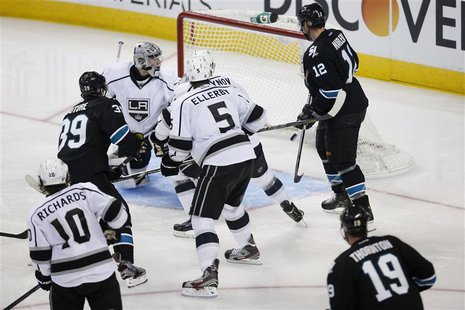 Members of the Los Angeles Kings and San Jose Sharks react as the game-winning puck shot by Sharks' Logan Couture (39) enters the goal in th