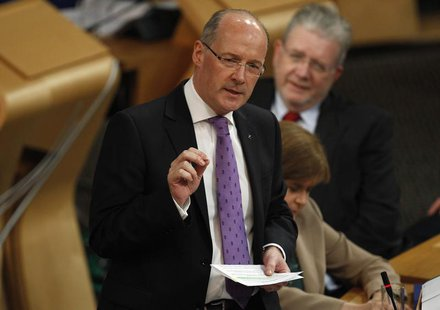 Scotland's Finance Secretary John Swinney gestures during his draft budget address in the debating chamber of the Scottish Parliament in Edi