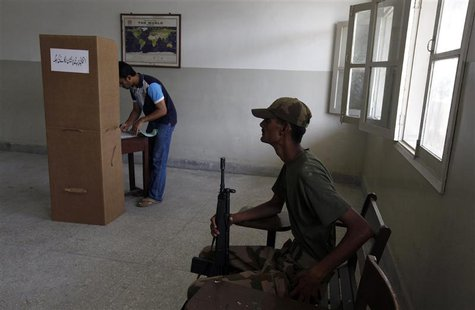 An army soldier (R) sits on a chair while a voter stamps his ballot papers inside a booth at a polling station during a re-polling for the g