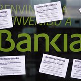 "A vandalized Bankia's bank office with papers stuck on it, is seen in Barcelona May 16, 2013. The papers read as ""Spanish 'corrallito' of La"