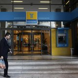 A man walks outside of the Hellenic Postbank's headquarters in Athens January 4, 2013. REUTERS/John Kolesidis