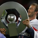 Paris Saint-Germain's David Beckham raises the French Championship trophy at the end of their team's French Ligue 1 soccer match against Bre