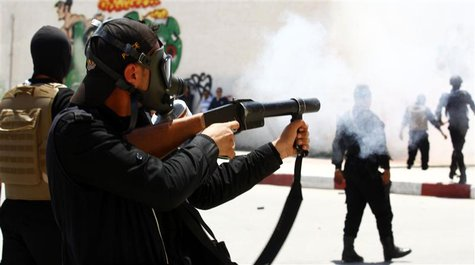 A police officer fires tear gas to break up a protest in the city of Kairouan May 19, 2013. REUTERS/Zoubeir Souissi