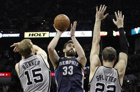Memphis Grizzlies center Marc Gasol (C) shoots against San Antonio Spurs forward Matt Bonner (L) and center Tiago Splitter during the second