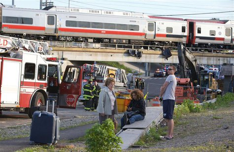 Passengers wait to be picked-up after two commuter trains collided in Bridgeport, Connecticut causing one to derail injuring numerous passen