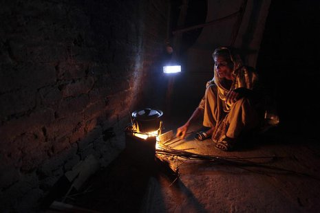A woman cooks over a wood-burning fire under a battery-run emergency light during a power outage in a slum in Islamabad April 29, 2013. REUT