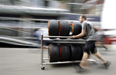 A Petronas mechanic pushes a trolley with Pirelli tires in the paddock ahead of the Spanish Formula One Grand Prix at the Circuit de Catalun