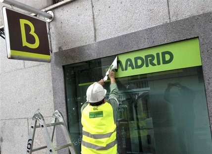 A worker removes a Caja Madrid signage to replace it with Bankia logos at a Bankia branch in Madrid May 20, 2013. REUTERS/Paul Hanna
