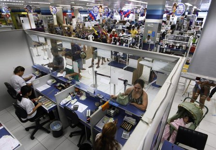 People wait in line at a branch of Bradesco bank, inside a Casas Bahia store in Sao Paulo February 18, 2013. REUTERS/ Nacho Doce