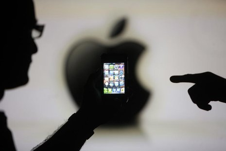 Men are silhouetted against a video screen with an Apple logo as they pose with an Apple iPhone 4 smartphone in this photo illustration take