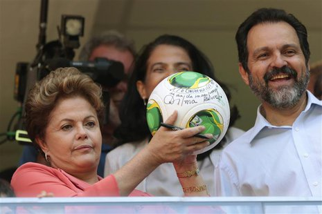 Brazil's President Dilma Rousseff (L) shows her autograph on a soccer ball as she stands beside Brasilia's Governor Agnelo Queiroz (R) durin