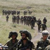 Israeli soldiers walk together during a training close to the ceasefire line between Israel and Syria on the Israeli occupied Golan Heights