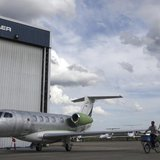A worker rides a bicycle around the hangars next to a private jet at the Embraer headquarters in Sao Jose dos Campos, 100 km (62 miles) from