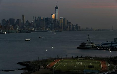 People play soccer on a pitch on the banks of the Hudson River in front of the New York City skyline as seen from Weehawken, New Jersey, Apr