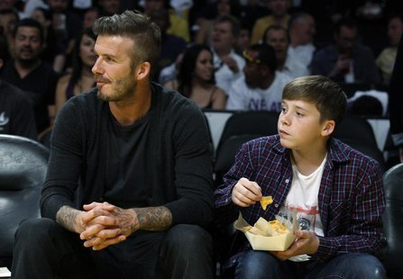 Soccer star David Beckham (L) and his son Brooklyn watch the Los Angeles Lakers play the Denver Nuggets during Game 1 of their first round N
