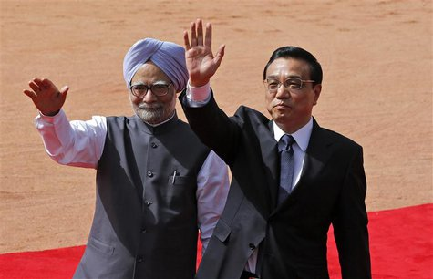 Chinese Premier Li Keqiang (R) and India's Prime Minister Manmohan Singh wave towards the media during Li's ceremonial reception at the fore