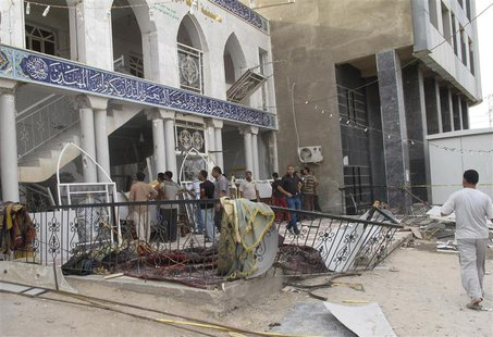 Onlookers gather outside Zain al-Abideen mosque, a Shiite place of worship, to inspect damage a day after a suicide bomb attack in Hilla, 10