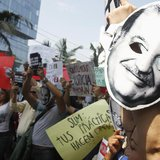 People protest holding masks printed with the face of Mexican telecommunications and retail tycoon Carlos Slim as he attends the Meeting of