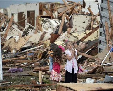 Two girls stand in rubble after a tornado struck Moore, Oklahoma, May 20, 2013.  REUTERS/Gene Blevins