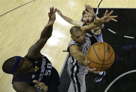 San Antonio Spurs forward Tim Duncan goes up for the shot as he is defended by Memphis Grizzlies forward Zach Randolph and center Marc Gasol