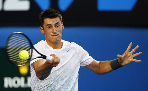 Bernard Tomic of Australia hits a return to Roger Federer of Switzerland during their men's singles match at the Australian Open tennis tour