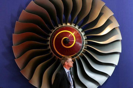 An exhibitor stands in front of a booth displaying Rolls-Royce aircraft engines on the first day of the 6th China International Aviation & A