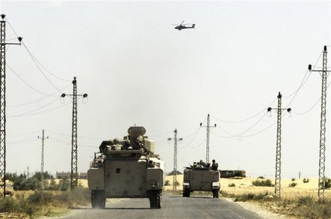 A helicopter flies overhead as soldiers in military vehicles proceed towards al-Jura district in El-Arish city from Sheikh Zuwaid, around 35