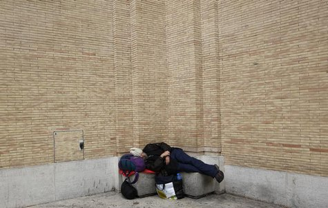 A homeless man sleeps in front of Saint Peter's Square in Rome March 7, 2013. REUTERS/Max Rossi