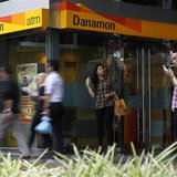 A man smokes a cigarette near a Danamon Bank ATM in Jakarta May 22, 2013. REUTERS/Beawiharta