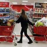 "A woman pulls shopping carts through the aisle of a Target store on the shopping day dubbed ""Black Friday"" in Torrington, Connecticut Novemb"