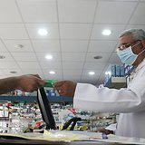 A man, wearing a surgical mask as a precautionary measure against the novel coronavirus, pays for medicine at a hospital pharmacy in Khobar