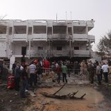 People stand among debris outside the French embassy after the building was attacked, in Tripoli April 23, 2013. REUTERS/Ismail Zitouny
