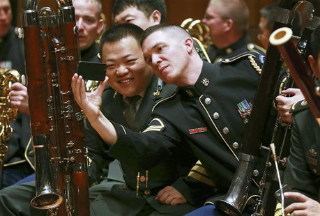 Musicians from the military bands of China's People's Liberation Army and the U.S. Army take photos during a rehearsal for their joint conce