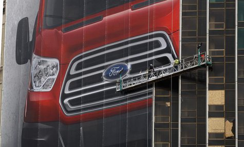 Workers hang a Ford Motor banner on the side of a building across from Cobo Center in advance of the media preview of the North American Int