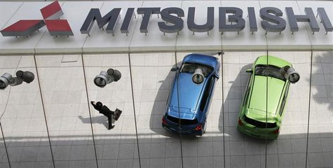 Mitsubishi Motors Corp's vehicles and a passer-by are reflected on an external wall at the company headquarters in Tokyo April 25, 2013. REU