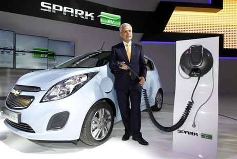 Sergio Rocha, president and CEO of GM Korea poses next to Spark EV at the Seoul motor show in Goyang, north of Seoul March 28, 2013. REUTERS