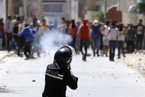 A riot police officer fires teargas during clashes with supporters of Islamist group Ansar al-Sharia at Hai al Tadamon in Tunis May 19, 2013
