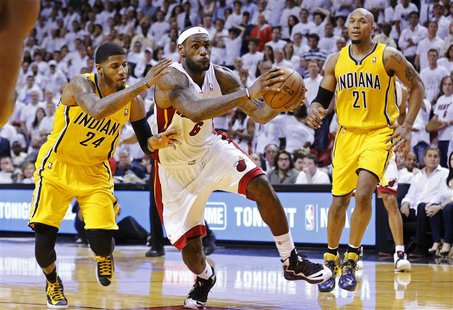 Miami Heat's LeBron James (C) drives through the defense of Indiana Pacers' Paul George (L) and David West on his way to making the game-win