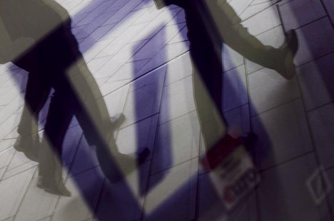 Pedestrians are reflected in a window as they walk in front of the headquarters of Deutsche Bank AG in Frankfurt September 5, 2011. REUTERS/