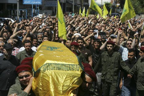 Supporters of Hezbollah and relatives of Hezbollah member Hussein Ahmad Abu Hasan carry his coffin during his funeral in Beirut's suburbs Ma