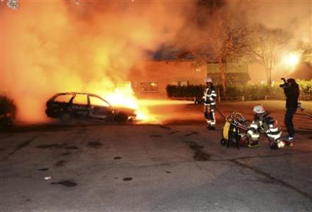 Firefighters extinguish a burning car, following riots in the Stockholm suburb of Kista late May 21, 2013, in this picture provided by Scanpix.  REUTERS/Fredrik Sandberg/Scanpix