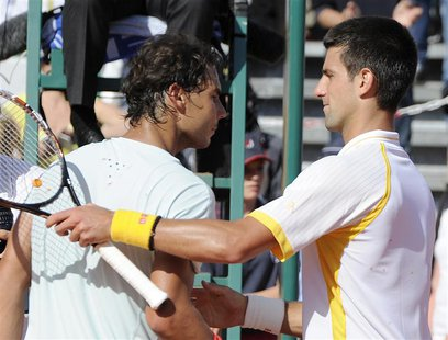 Novak Djokovic of Serbia (R) shakes hand with Rafael Nadal of Spain after the final match of the Monte Carlo Masters in Monaco April 21, 201