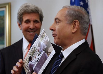 Israeli Prime Minster Benjamin Netanyahu (R) shows a present given to him by U.S. Secretary of State John Kerry in Jerusalem May 23, 2013. R