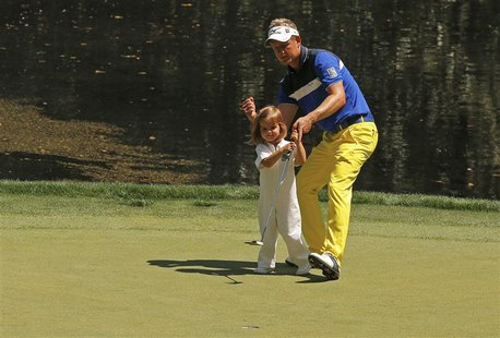 Britain's Luke Donald reacts after his daughter Ellie holed a putt on the 9th green during the annual Masters Par 3 Contest at the Augusta N