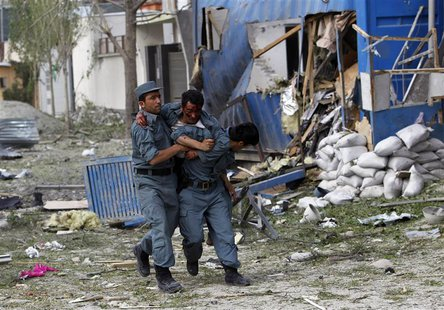 A wounded Afghan policeman (C) is helped away from the site of an explosion in Kabul May 24, 2013. REUTERS/Omar Sobhani