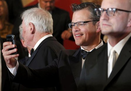 "Cast member Matt Damon (C) takes pictures with his mobile phone after the screening of the film ""Behind the Candelabra"" by Steven Soderbergh"