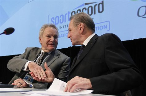 International Olympic Committee (IOC) President Jacques Rogge (R) shakes hands with IOC executive Denis Oswald during an IOC executive board