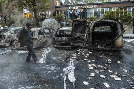 A bystander checks the debris around a row of burnt cars in the suburb of Rinkeby after youths rioted in several different suburbs around St