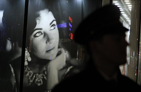 A security guard walks past an image of Elizabeth Taylor outside Christie's auction house during an auction of the late actress' jewelry, cl