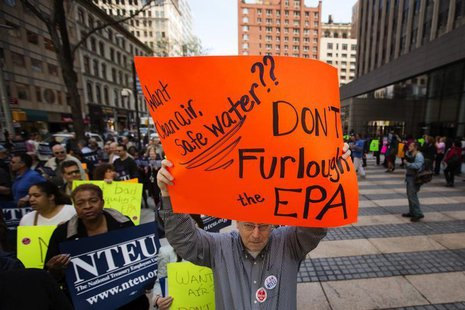 A federal employee holds up a sign protesting the effects of sequestration and the practice of furloughs at a gathering in New York, May 7,